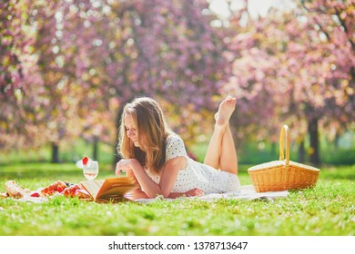 Beautiful young woman having picnic on sunny spring day in park during cherry blossom season, reading book