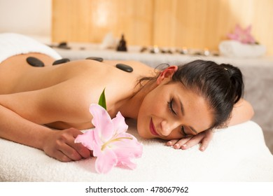 Beautiful young woman having a rejuvenating massage in a wellness studio - spa