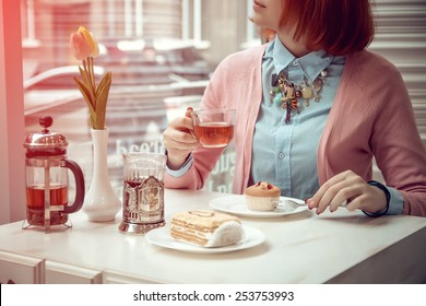 beautiful young woman is having tee and cake in a nice cafe. Photos in purple tones
