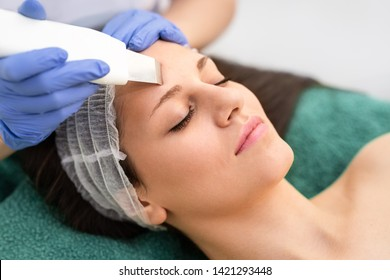 Beautiful young woman having ultrasound cleansing treatment facial procedure by professional cosmetologist at beauty salon spa center skincare