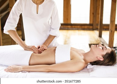 Beautiful young woman having visceral massage in spa center