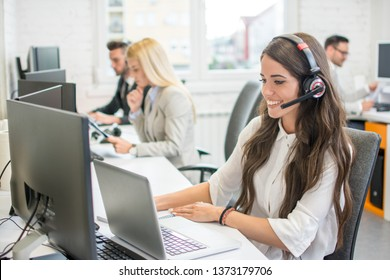 Beautiful young woman with headset using laptop while talking with client. Online customer support.