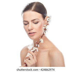 beautiful young woman with healthy face and clean skin holding sakura branch isolated on white background