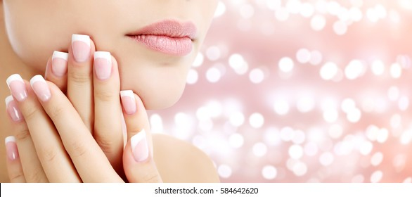 Beautiful young woman with healthy skin and french manicure on an abstract background with blurred lights