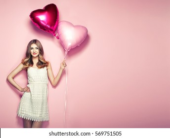 Beautiful young woman with heart shape air balloon on color background. Woman on Valentine's Day. Symbol of love