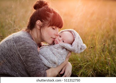 Beautiful young woman with her adorable little son at sunny park or meadow in sunset. Young mother holding her newborn baby. Mother and new born boy having good time in the nature. Color toned image.