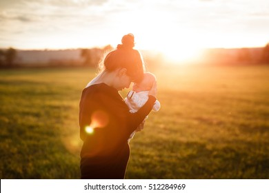 Beautiful young woman with her adorable little son at sunny in the meadow in sunset. Young mother holding her newborn baby. Mother and new born boy having good time in the nature. Color toned image.