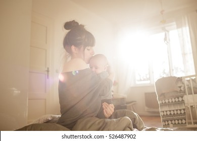 Beautiful young woman with her adorable little son on the bed at home. Young mother kissing her newborn baby. Mother and little boy having good time. Strong sun light from window. Color toned image.