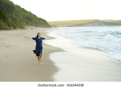 Beautiful young woman with her arms up running on and enjoying the sense of freedom on a desolate beach.
