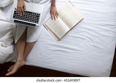 Beautiful young woman in her bed while checking her laptop at home.