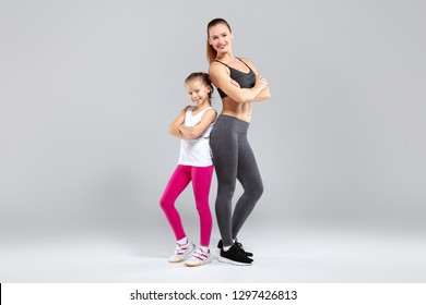 Beautiful young woman and her charming daughter standing together in sportwear