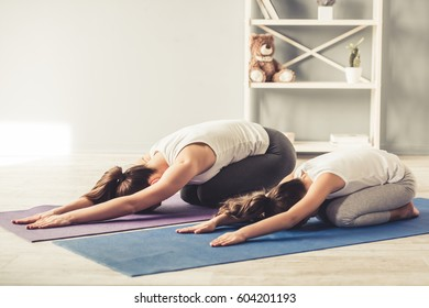 Beautiful young woman and her charming little daughter are doing yoga together at home