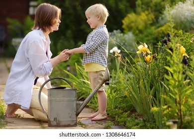 Beautiful young woman and her cute son watering plants in the garden at summer sunny day. Gardening activity with little kid and family