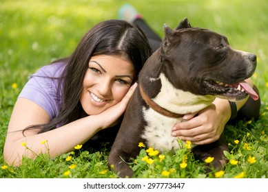 Beautiful young woman with her cute stafford terrier lying on grass in the park. Looking at camera.