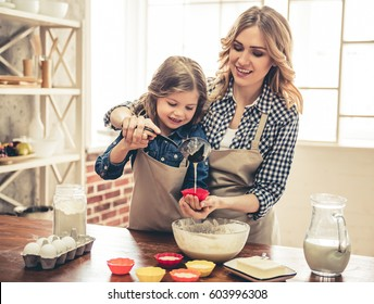 Beautiful young woman and her cute little daughter in aprons are smiling while filling muffin cases