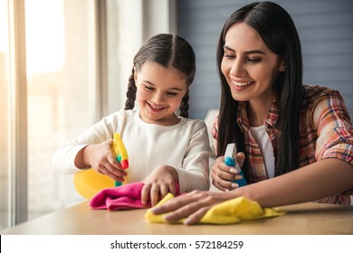 Beautiful young woman and her daughter in protective gloves are smiling, using detergent and dusters while cleaning furniture at home