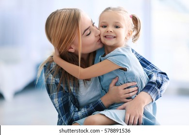 Beautiful young woman and her daughter at home. Mother's day concept