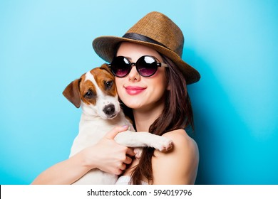 beautiful young woman with her dog standing in front of wonderful blue background