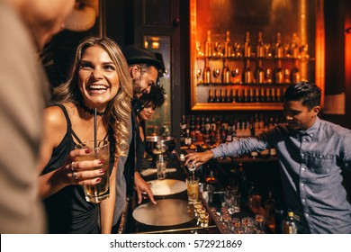 Beautiful young woman with her friends at bar. Young people enjoying a night at club.