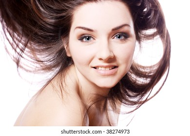 A beautiful young woman with her hair in motion, smiling on a white background.