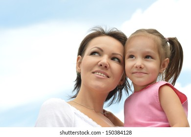 Beautiful young woman and her little daughter on the sky background