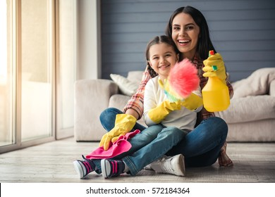 Beautiful young woman and her little daughter are sitting on the floor and smiling while cleaning their home