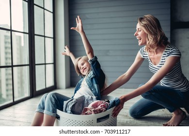 Beautiful young woman  and her little cheerful daughter are having fun while doing cleaning at home. Holding cleaning tools and smiling.