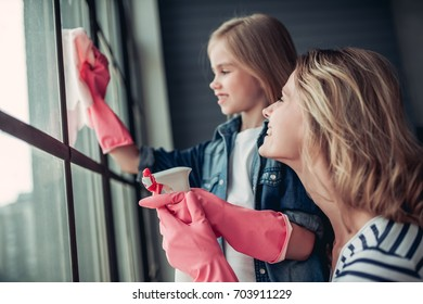 Beautiful young woman  and her little cheerful daughter are doing cleaning at home. Holding cleaning tools and smiling.