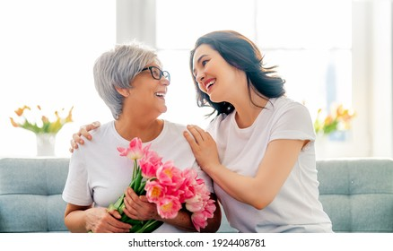 Beautiful young woman and her mother with flowers tulips in hands at home.
