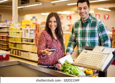 Beautiful young woman and her partner paying for groceries at the cash register with a credit card