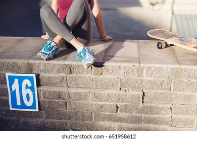 Beautiful young woman with her skateboard in the city in sunny weather