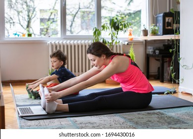 Beautiful Young Woman and her Son Exercising Pilates, Yoga, Fitness at Home Looking at the Laptop