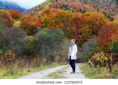 Beautiful young woman hikes in the forest in the mountains of the Rila Nature Park in Bulgaria with vibrant autumn colors