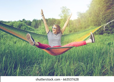Beautiful young woman hippy on a hammock in a green summer field and forest, freedom, vacations, fun concept