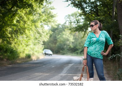 Beautiful young woman hitchhiking on the road