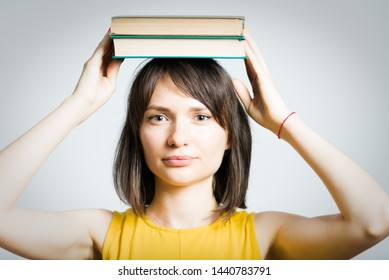 beautiful young woman hold books on head isolated on background