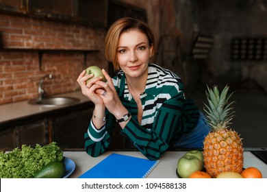 Beautiful young woman holding apple and looking to camera in her modern loft kitchen. Fitness coach. Healthy food concept.