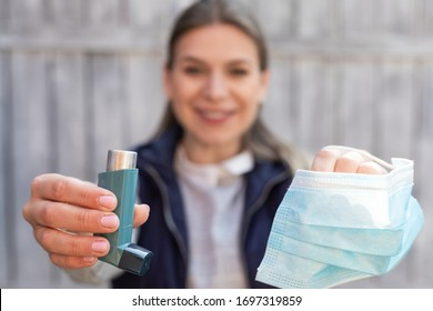 Beautiful young woman holding asthma inhaler and surgical mask outdoor
