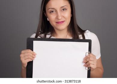 Beautiful young woman holding a billboard sign. Studio shot