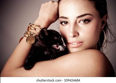 beautiful young woman holding black kitten, studio shot