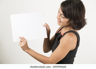 Beautiful young woman holding a blank sheet of paper. Space for your text. Isolated on white.