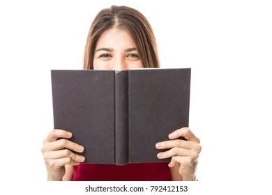 Beautiful young woman holding a book in front of her and making eye contact on a white background