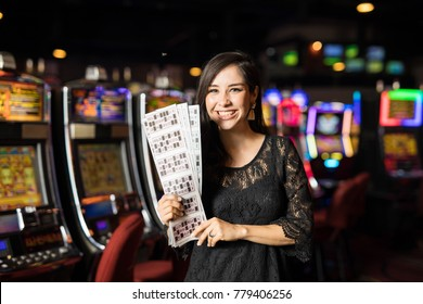Beautiful young woman holding a bunch of lottery and bingo tickets after winning, with slot machines in the background