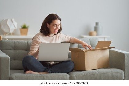 Beautiful young woman is holding cardboard box sitting on sofa at home.