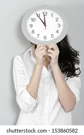 Beautiful young woman holding up a clock face
