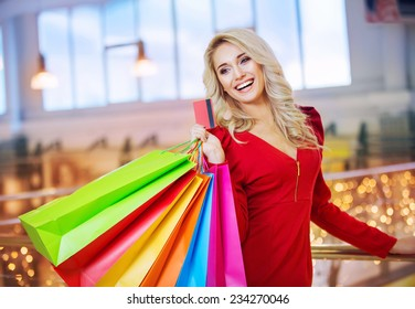 beautiful young woman holding colored shopping bags and credit card in the shopping mall on sales