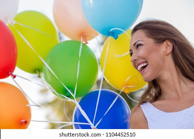 Beautiful young woman holding colorful balloons while smiling daytime