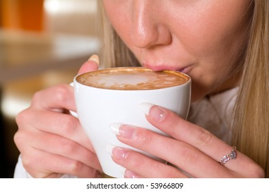 beautiful young woman holding a cup of hot drink