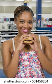Beautiful young woman holding a delicious cheeseburger