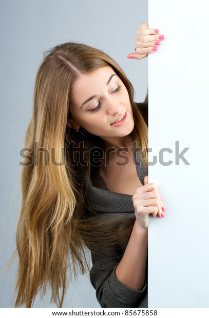 Beautiful young woman holding an empty billboard